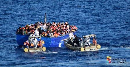 Migrants sit in their boat during a rescue operation by Italian navy ship Borsini off the coast of Sicily