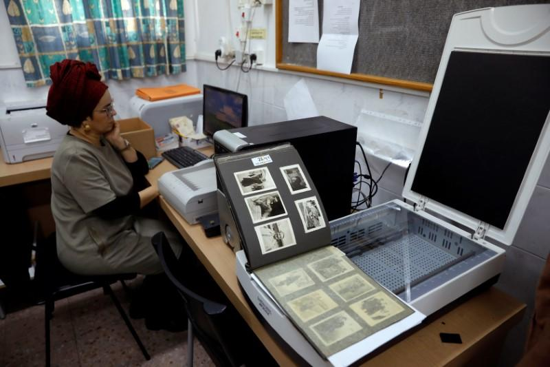 A employee demonstrates the scanning process of photographs during an interview with Reuters at the offices of Shem Olam Holocaust Memorial Centre in Kfar Haroeh, Israel