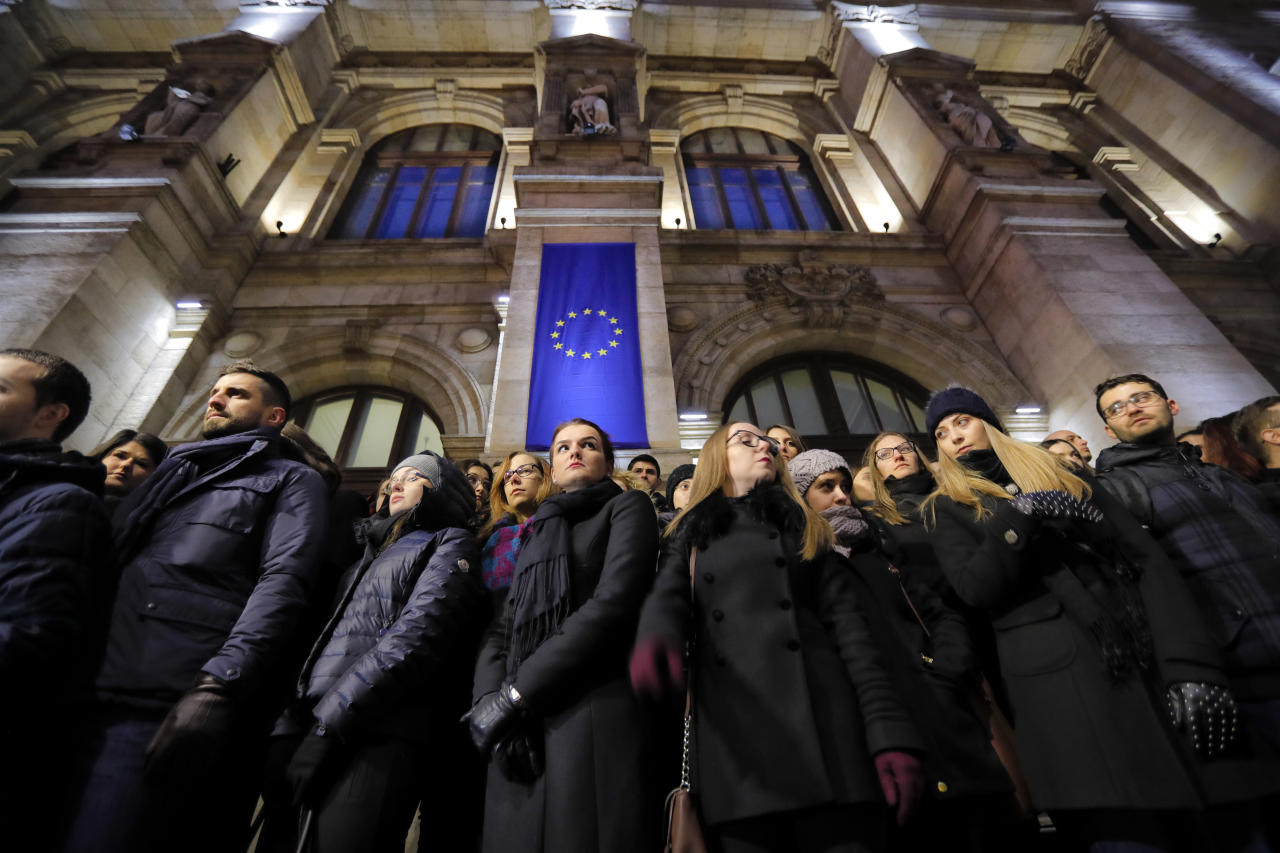 Romanian magistrates stand during a silent protest outside the Bucharest Court of Appeal in Bucharest, Romania, Monday, Dec. 18, 2017. Hundreds of Romanian judges and prosecutors staged protests around the country over planned modifications to the legal system they say will hamper prosecutions. (AP Photo/Vadim Ghirda)