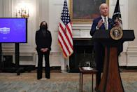 US President Joe Biden speaks about his Covid-19 response before signing executive orders, as Vice President Kamala Harris looks at the White House on January 22, 2021