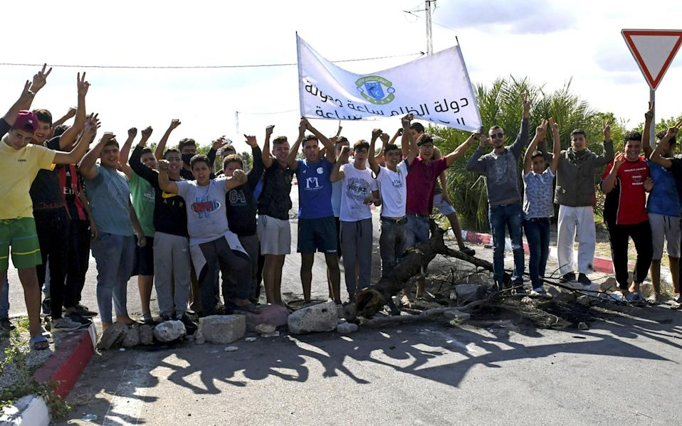 Tunisian youths prepare to burn tyres and block the road leading to Chebba to protest against the decision of the Tunisian Football Federation to freeze the activities of their team - AFP