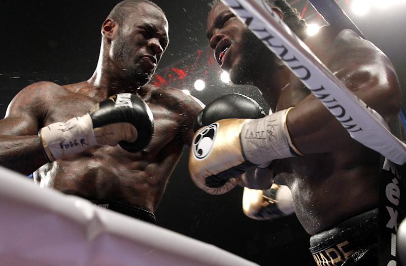 Deontay Wilder (L) punches WBC heavyweight champion Bermane Stiverne against the ropes during their title fight at the MGM Grand Garden Arena on January 17, 2015 in Las Vegas, Nevada (AFP Photo/Steve Marcus)