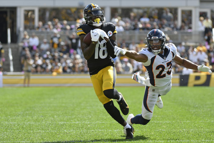 Pittsburgh Steelers wide receiver Diontae Johnson (18) hauls in a pass from quarterback Ben Roethlisberger with Denver Broncos cornerback Kyle Fuller (23) defending during the first half of an NFL football game against the Denver Broncos in Pittsburgh, Sunday, Oct. 10, 2021. Johnson took the ball in for a touchdown. (AP Photo/Don Wright)