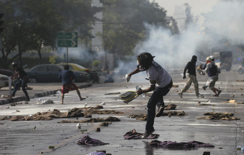 Anti-government protesters throw a tear gas canister back at riot police near a gymnasium in Bangkok, Thailand, Thursday, Dec. 26, 2013. Officers fired tear gas and rubber bullets toward protesters trying to force their way into a sports stadium where candidates were gathering to draw lots for their position on polling papers. (AP photo/Sakchai Lalit)