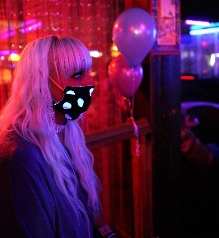 "Echo, a worker at The Den strip club in Cheyenne, Wyoming, watches performers onstage during the club's reopening Friday night. The club hosted a ""masks on, clothes off"" party to celebrate."