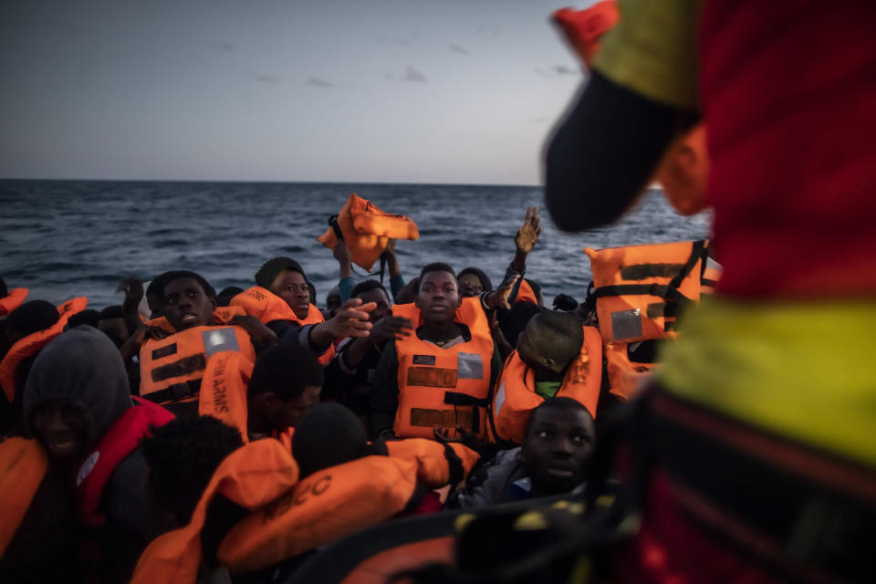 14-year old Bamba Bourahima from Ivory Coast, centre, waits to receive a life vest as rescuer Alberto Agrelo distributes them to all the migrants aboard an overcrowded rubber boat after being rescued by the Spanish NGO Open Arms rescue vessel in the Mediterranean Sea, international waters, at 80 miles off the Libyan coast, Saturday Feb. 13, 2021. Various African migrants drifting in the Mediterranean Sea after fleeing Libya on unseaworthy boats have been rescued. In recent days, the Libyans had already thwarted eight rescue attempts by the Open Arms, a Spanish NGO vessel, harassing and threatening its crew in international waters. (AP Photo/Bruno Thevenin)