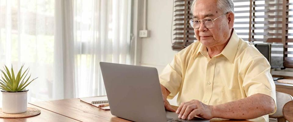 Older man types on laptop, sitting at kitchen table