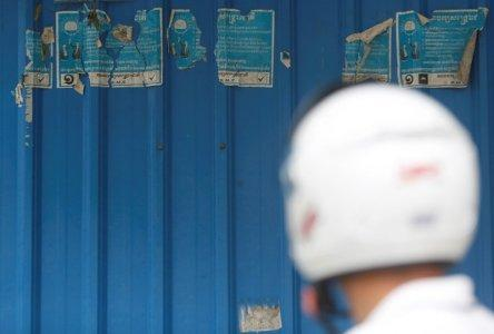 A man stands near posters the Cambodia National Rescue Party (CNRP) on the outskirts of Phnom Penh, Cambodia, November 20, 2017. REUTERS/Samrang Pring