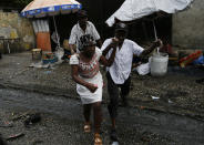 A Haitian couple jumps over running wastewater in Port-au-Prince, Haiti, Friday, July 9, 2021, two days after Haitian President Jovenel Moise was assassinated in his home. (AP Photo/Fernando Llano)