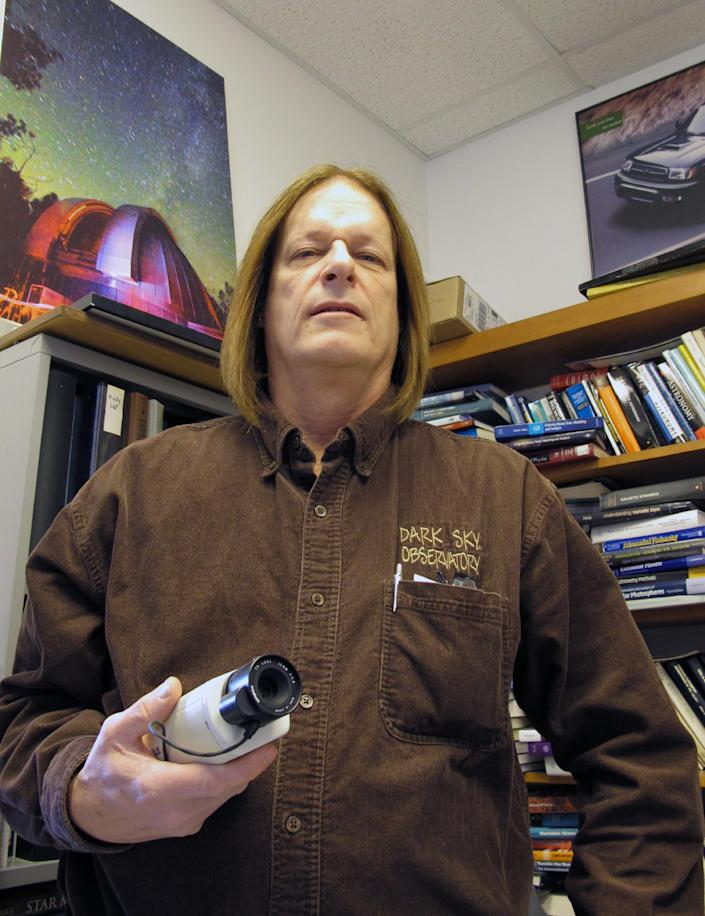 In this Feb. 25, 2012, photo, astronomy professor Daniel Caton poses for a photo with a low-light video camera in his office at Appalachian State University in Boone, N.C. Caton is hoping to use the cameras to capture a phenomenon known as the Brown Mountain lights. (AP Photo/Allen Breed)