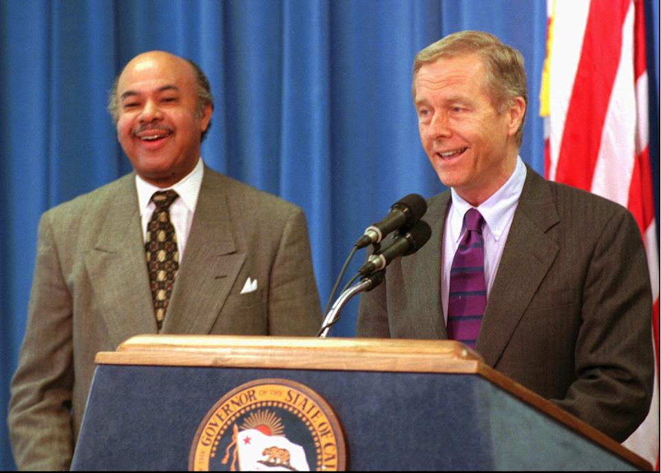 Gov. Pete Wilson, right, and Ward Connerly, who in 1996 led the fight to pass Proposition 209, smile as they talk to reporters in Sacramento, California in 1997. Prop 209 amended the state constitution to ban affirmative action practices in public education and hiring. This election day, state voters will pass judgment on Prop 16, which would repeal Prop 209. Connerly is staunchly opposed to 16.