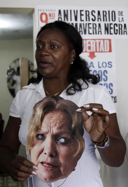 Berta Soler, leader of the Cuban dissident group Ladies in White, shows a mask of Laura Pollan after being freed from detention in Havana, Cuba, Monday March 19, 2012. Soler and dozens of supporters of the Ladies in White were taken into custody early Sunday. Pollan is the group's former leader and co-founder who died in 2011 of a heart attack. (AP Photo/Franklin Reyes