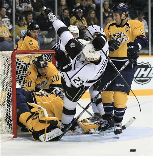 Los Angeles Kings right wing Dustin Brown (23) is pushed away from Nashville Predators goalie Pekka Rinne (35), of Finland, by Predators defenseman Shea Weber (6) in the first period of an NHL hockey game Monday, Feb. 27, 2012, in Nashville, Tenn. Behind Rinne are Predators' Ryan Suter (20) and Mike Fisher (12). (AP Photo/Mark Humphrey)