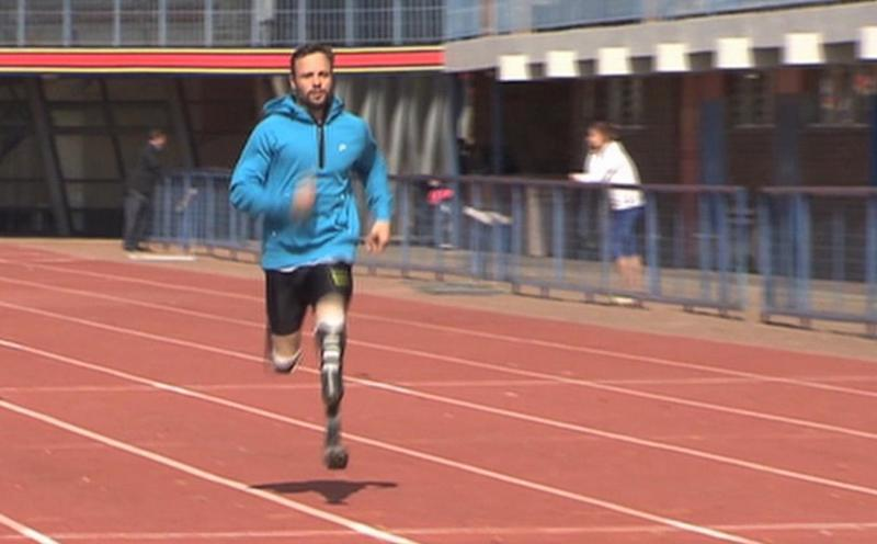 "In this image taken on Thursday June 27, 2013 from TV provided by ab productions via APTN, Oscar Pistorius runs at the University of Pretoria, South Africa, during his first track training session since the killing of girlfriend Reeva Steenkamp. With a short beard and a blue hooded Nike sports top, the lean-looking double-amputee Olympian did some light jogging at his first formal session in around five months. He then described his return to a regular track routine as ""bittersweet"" to his agent. (AP Photo/ab productions via APTN)"
