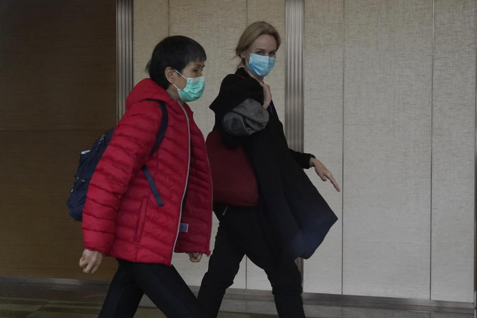 Thea Fischer, right, of the World Health Organization team walks down a corridor after meetings with the Chinese side in the cordoned wing of their hotel in Wuhan in central China's Hubei province on Friday, Feb. 5, 2021. World Health Organization investigators looking for clues into the origin of the coronavirus in the central Chinese city of Wuhan said that the Chinese side has provided a high level of cooperation, but cautioned against expecting immediate results from the visit. (AP Photo/Ng Han Guan)