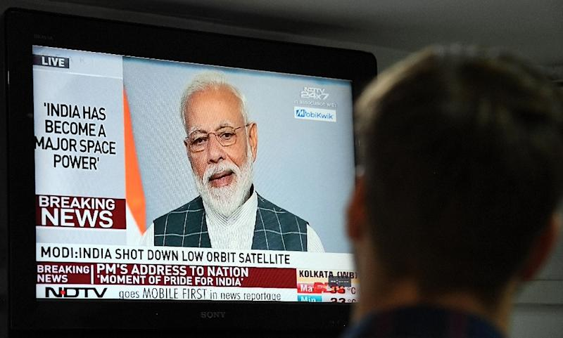 A man watches Indian Prime Minister Narendra Modi's address to the nation on a local news channel declaring his country is a space power after destroying a low-orbiting satellite (AFP Photo/Prakash SINGH)