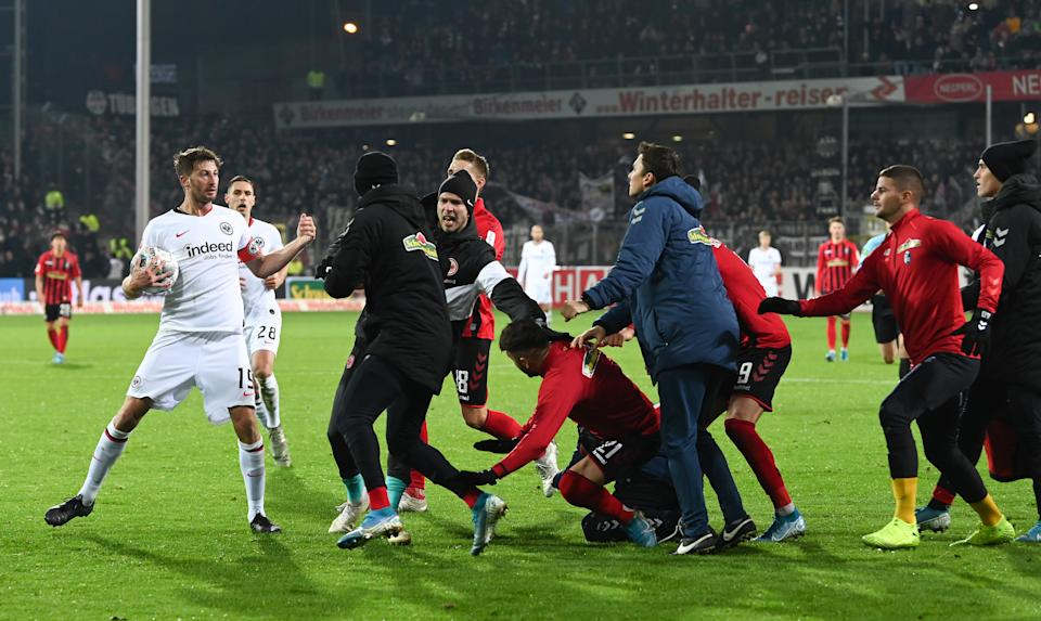 Team members of SC Freiburg trying to confront David Angel Abraham (L) of Eintracht Frankfurt during the Bundesliga match between Sport-Club Freiburg and Eintracht Frankfurt at Schwarzwald-Stadion on November 10, 2019 in Freiburg im Breisgau, Germany.