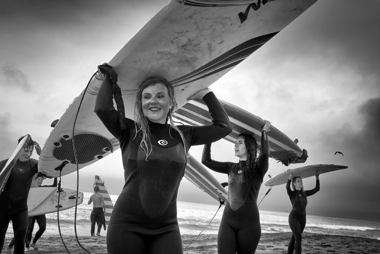 <p>After an exhausting but satisfying surfing lesson on a stormy spring afternoon, a group of teens on a class trip walks back from the ocean carrying their surfboards on their heads. (© Dotan Saguy) </p>