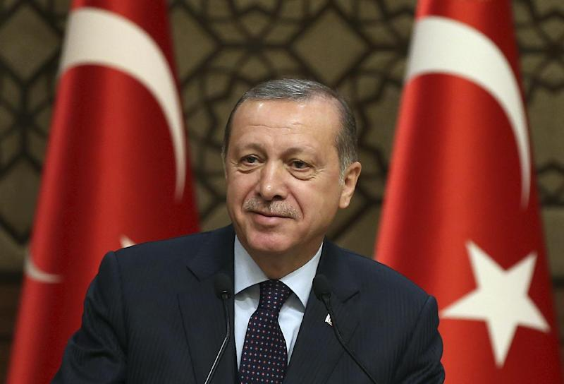 Turkey's President Recep Tayyip Erdogan smiles, during a meeting with local media representatives, in Ankara, Turkey, Wednesday, March 22, 2017. Tensions between Turkey and Europe have boiled in recent weeks, but acrimony over Turkey's belief that some European countries are harboring suspected terrorists has festered for years. Erdogan criticized Germany Wednesday for allowing a weekend rally of Kurds, some of whom expressed support for a jailed rebel leader in Turkey.(Yasin Bulbul/Presidential Press Service, Pool Photo via AP)