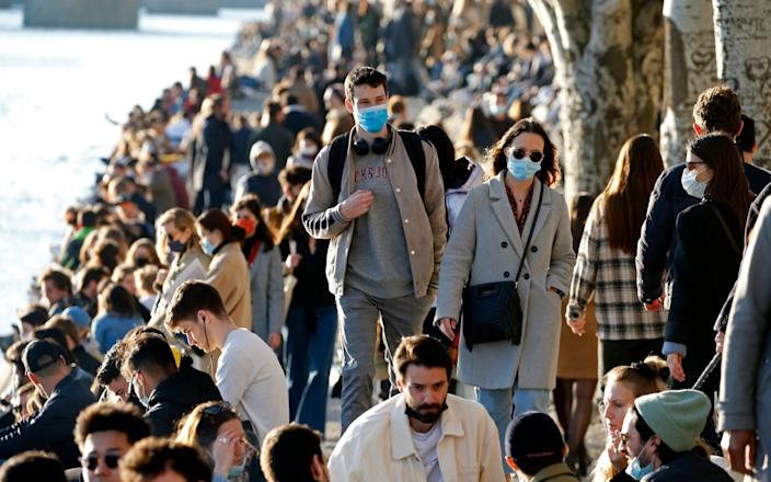 People gather on the banks of the Seine river to enjoy the sun before the 6pm curfew - Getty