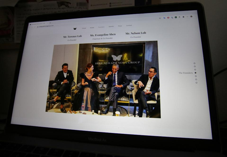 A photo on the website of Bellagraph Nova Group, showing owners Terence (R) and Nelson (L) Loh and Evangeline Shen sitting next to former U.S. President Barack Obama, is pictured on screen, in Singapore August 19, 2020. REUTERS/Ng Yi Shu