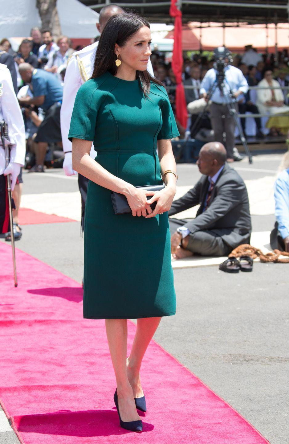 """<p>On her final day in Fiji, the Duchess wore a<a href=""""https://www.townandcountrymag.com/style/fashion-trends/a24175133/meghan-markle-green-jason-wu-dress-final-day-fiji/"""" rel=""""nofollow noopener"""" target=""""_blank"""" data-ylk=""""slk:green mid-length dress"""" class=""""link rapid-noclick-resp""""> green mid-length dress</a> by Jason Wu, gold drop earrings, and black pumps to the unveiling of the Labalaba Statue. </p>"""