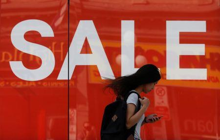 A woman looks at her phone while walking past a sales sign on display outside a retail store in Ottawa