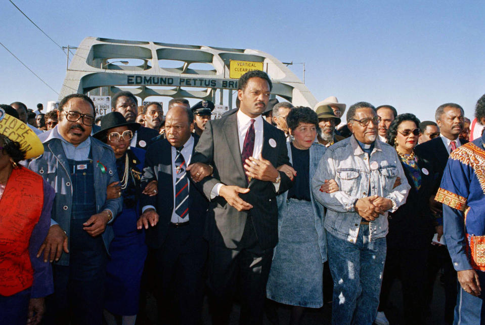 "FILE - In this March 4, 1990, file photo, civil rights figures lead marchers across the Edmund Pettus Bridge during the recreation of the 1965 Selma to Montgomery march in Selma, Ala. From left are Hosea Williams of Atlanta, Georgia Congressman John Lewis, the Rev. Jesse Jackson, Evelyn Lowery, SCLC President Joseph Lowery and Coretta Scott King. This Sunday, March 7, 2021, marks the 56th anniversary of those marches and ""Bloody Sunday,"" when more than 500 demonstrators gathered on March 7, 1965, to demand the right to vote and cross Selma's Edmund Pettus Bridge. They were met by dozens of state troopers and many were severely beaten. (AP Photo/Jamie Sturtevant, File)"
