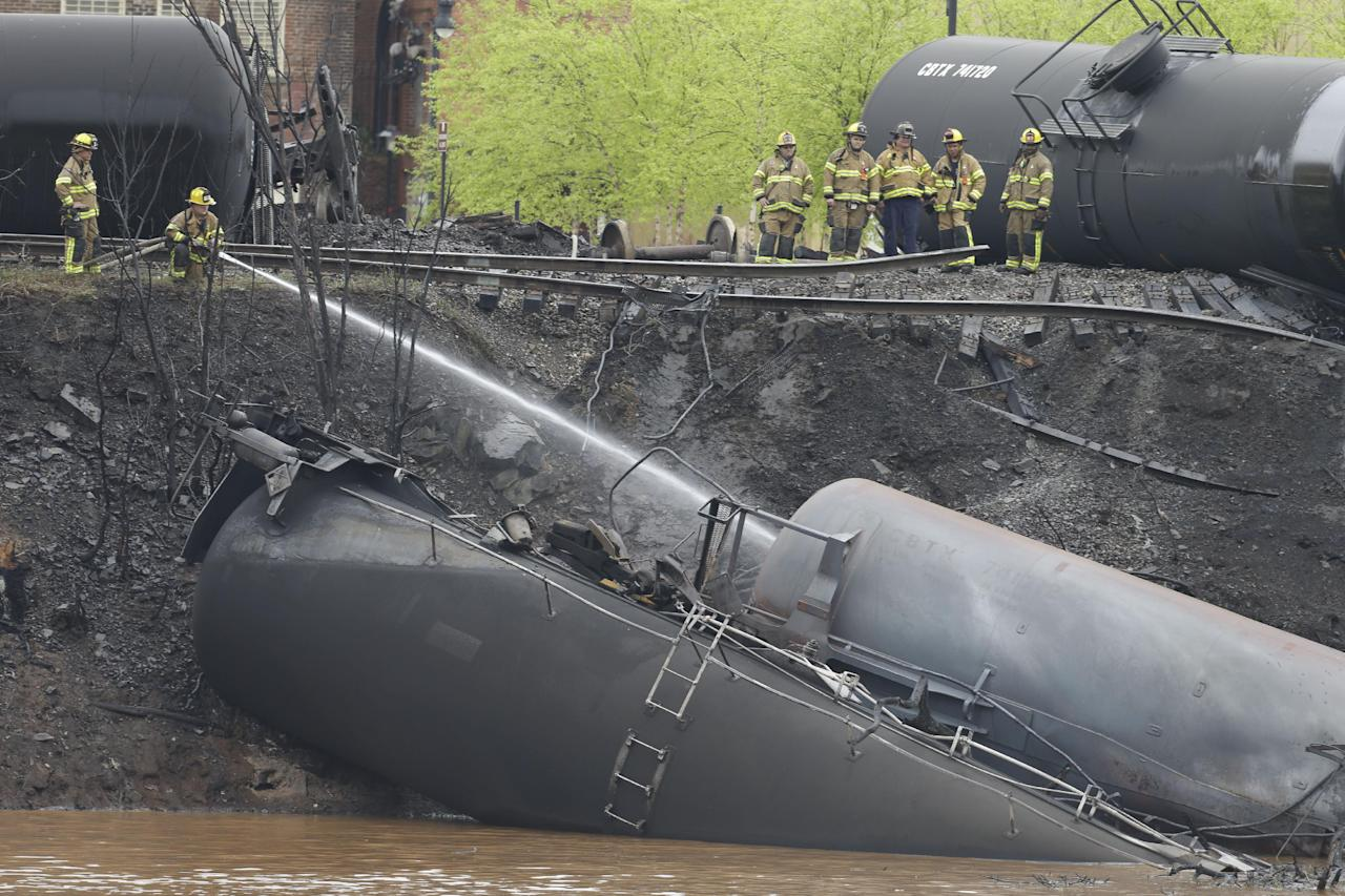 Firefighters and rescue workers work along the tracks where several CSX tanker cars carrying crude oil derailed and caught fire along the James River near downtown in Lynchburg, Va.., Wednesday, April 30, 2014. Police said that 13 or 14 tanker cars were involved in the derailment.(AP Photo/Steve Helber)