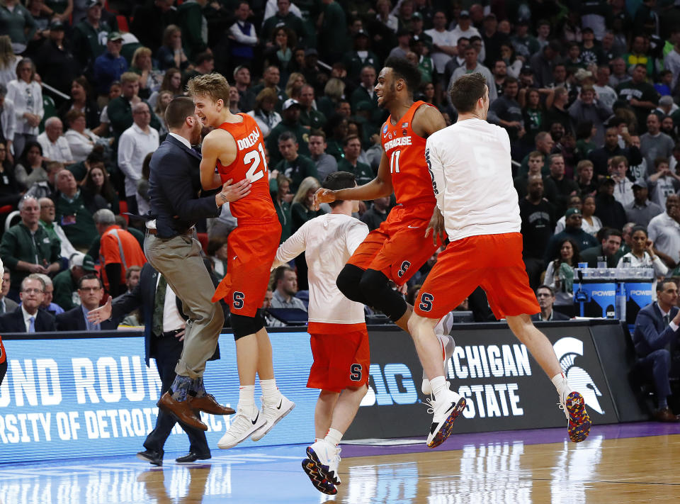 Syracuse players, including Marek Dolezaj (21) and Oshae Brissett (11), celebrate a 55-53 win over Michigan State in an NCAA men's college basketball tournament second-round game in Detroit, Sunday, March 18, 2018. (AP Photo/Paul Sancya)