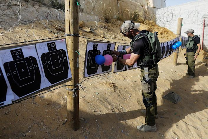 "<p>An Israeli instructor hangs up balloons on shooting targets as a group of tourists take part in a two hour ""boot camp"" experience, at ""Caliber 3 Israeli Counter Terror and Security Academy"" in the Gush Etzion settlement bloc south of Jerusalem in the occupied West Bank July 13, 2017. (Photo: Nir Elias/Reuters) </p>"