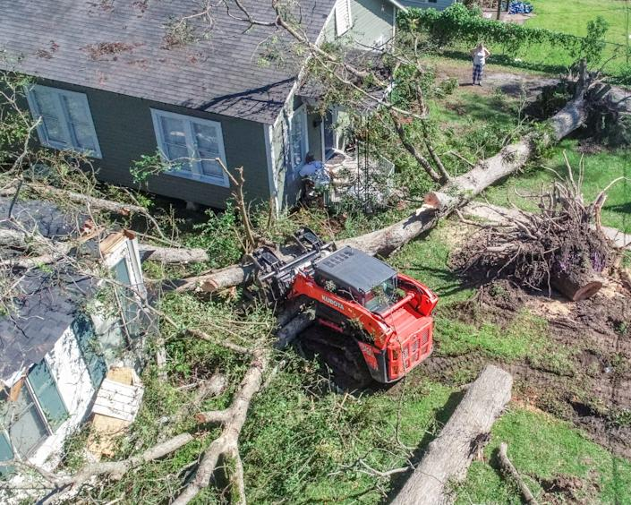 Arborist Michael McDonald on Saturday clears trees that fell on houses after Hurricane Delta made landfall in, Louisiana.