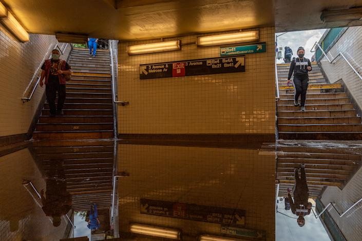 Commuters walk into the flooded Third Avenue/149th St. subway station in New York, N.Y., where service was disrupted.