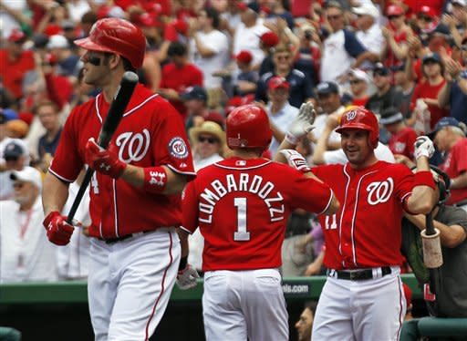 Washington Nationals' Stephen Lombardozzi, center, reacts with Ryan teammate Zimmerman after hitting a solo home run as Bryce Harper, left, heads to the batter's box to hit the first pitch for his own solo home run during the first inning of a baseball game with the Atlanta Braves, Sunday, June 3, 2012, in Washington. (AP Photo/Alex Brandon)