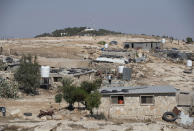 The Israeli settlement of Ma'on, in the background and overlooks the the West Bank Bedouin village of al-Mufagara, near Hebron, Thursday, Sept. 30, 2021. An Israeli settler attack last week damaged much of the village's fragile infrastructure. (AP Photo/Nasser Nasser)