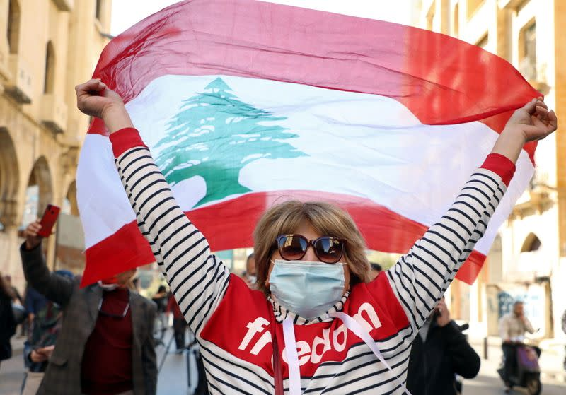 A demonstrator holds up a national flag during a protest in Beirut