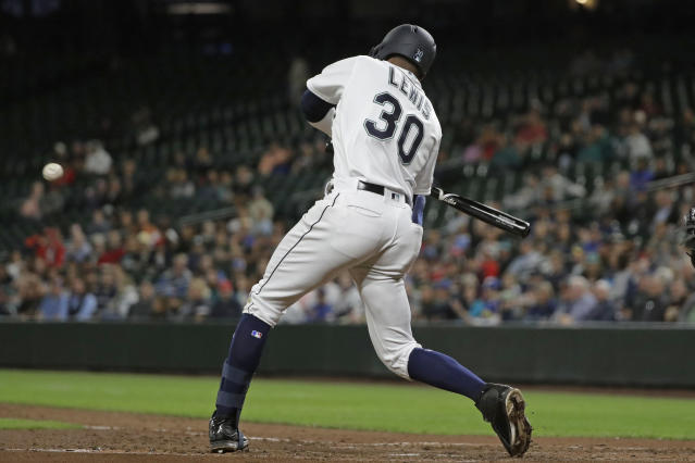 Seattle Mariners' Kyle Lewis begins his swing on a solo home run during the fifth inning of the team's baseball game against the Cincinnati Reds, Tuesday, Sept. 10, 2019, in Seattle during the second at-bat of his debut in the majors. (AP Photo/Ted S. Warren)