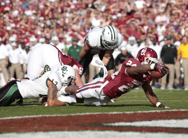 NORMAN, OK - NOVEMBER 10: Running back Brennan Clay #24 of the Oklahoma Sooners stretches for a touchdown during the game against the Baylor Bears November 10, 2012 at Gaylord Family-Oklahoma Memorial Stadium in Norman, Oklahoma. (Photo by Brett Deering/Getty Images)