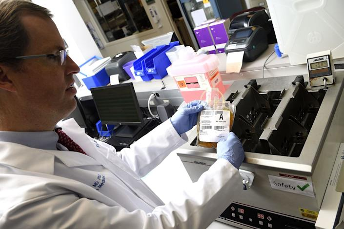 "Dr. Aaron Tobian, a pathologist and director of transfusion medicine at Johns Hopkins, removes a bag of donated COVID-19 convalescent plasma after it had thawed. <span class=""copyright"">(Will Kirk / Johns Hopkins University)</span>"