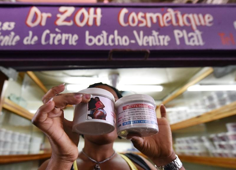 A woman shows pots of cream supposed to enhance bottoms in a market in Ivory Coast's Abidjan (AFP Photo/Sia Kambou)