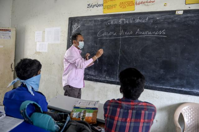 A teacher (C) wearing a facemask teaches as students attend the class at a governement-run high school in Secunderabad.