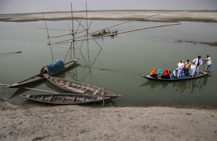 Health workers accompany elderly villagers in a boat as they cross the river Brahmaputra to reach a vaccination center for COVID-19 at Bahakajari village in an interior part of Indian northeastern state of Assam, India, Tuesday, March 23, 2021. (AP Photo/Anupam Nath)