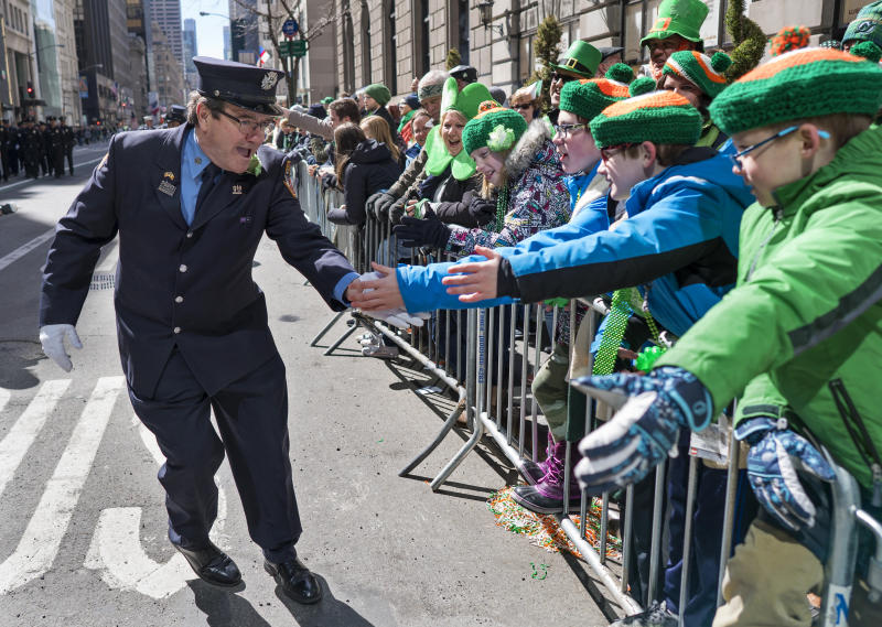 "A New York City firefighter greets spectators as they take part in the St. Patrick's Day parade Saturday, March 17, 2018, in New York. Several bagpipe bands led a parade made up of over 100 marching bands after Democratic Gov. Andrew Cuomo spoke briefly, calling it a ""day of inclusion"" and adding: ""We're all immigrants."" (AP Photo/Craig Ruttle)"