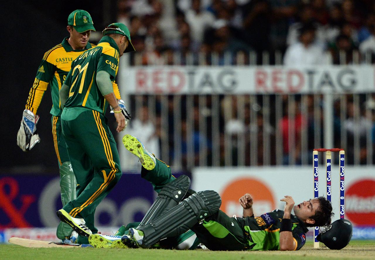 Pakistan's cricketer Ahmad Shehzad (R) lays on the ground after colliding with South African cricketer Faf Du Plessis during the first one-day in Sharjah Cricket Stadium in Sharjah on October 30, 2013. South African captain AB de Villiers won the toss and decided to bat in the first of five one-day internationals against Pakistan in Sharjah. AFP PHOTO/ASIF HASSAN        (Photo credit should read ASIF HASSAN/AFP/Getty Images)