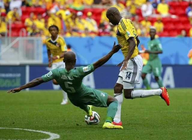 Ivory Coast's Didier Zokora (L) fights for the ball with Colombia's Victor Ibarbo during their 2014 World Cup Group C soccer match at the Brasilia national stadium in Brasilia June 19, 2014. REUTERS/Paul Hanna (BRAZIL - Tags: SOCCER SPORT WORLD CUP)