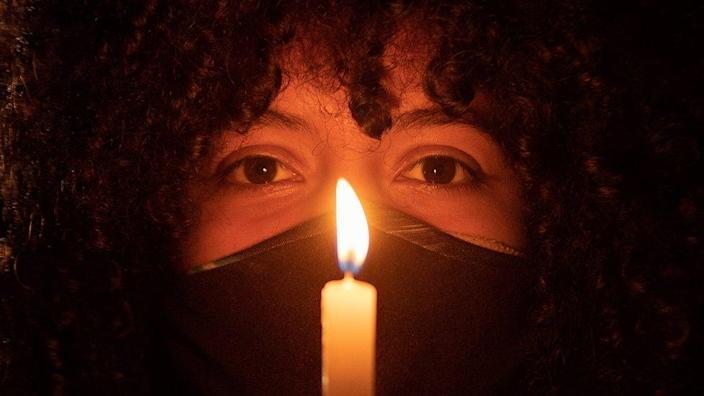 A woman holds a candle during a protest in Brasilia