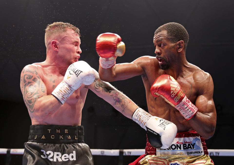 Jamel Herring of the United States, right, lands a blow on Britain's Carl Frampton during their WBO super-featherweight world title fight in Dubai, UAE, early Sunday April 4, 2021. (AP Photo/Kamran Jebreili)