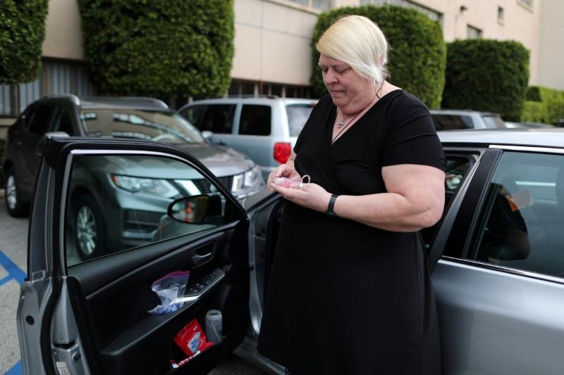 FILE PHOTO: Uber and Lyft driver Tammie Jean Lane, 60, who had part of her lung removed after lung cancer, holds a bottle of hand sanitizer during the global outbreak of coronavirus (COVID-19) in Los Angeles