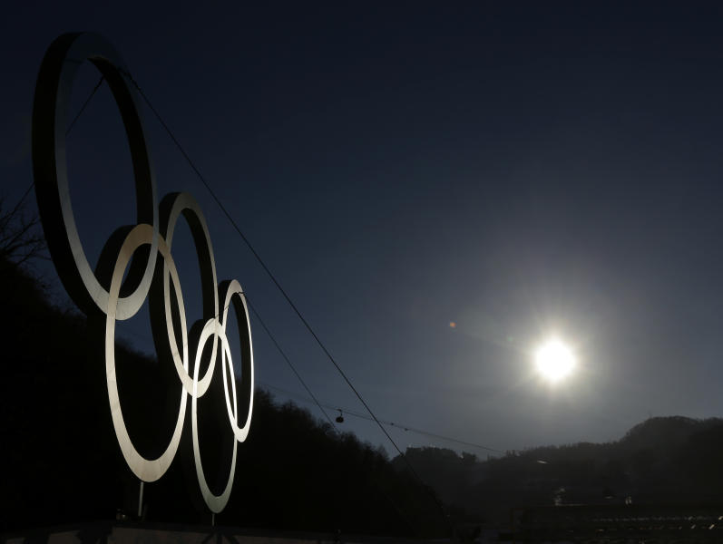 The sun rises above the Caucasus Mountains beyond a set of Olympic Rings Thursday, Feb. 6, 2014, in Rosa Khutor, Russia. The area will host the alpine events at the 2014 Winter Olympics which opens Friday, Feb. 7. (AP Photo/Charlie Riedel)