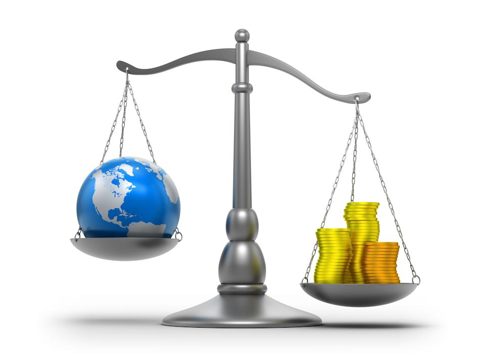 Scales with earth and money. Graphic: Getty